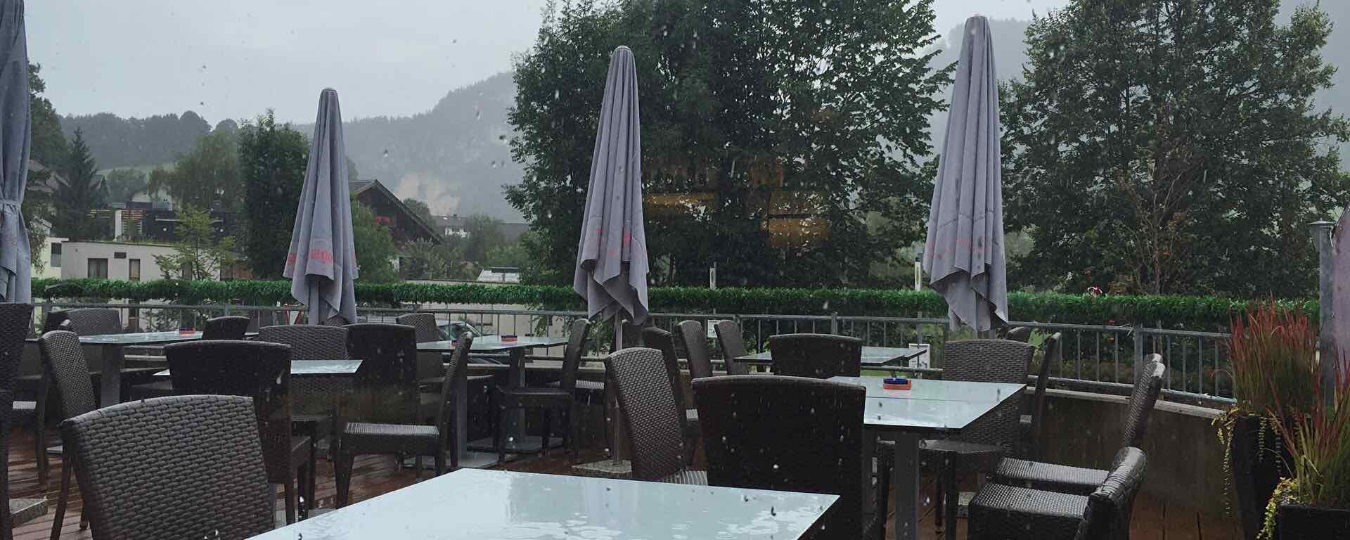 Terrasse eines Cafés in Tirol im Regen